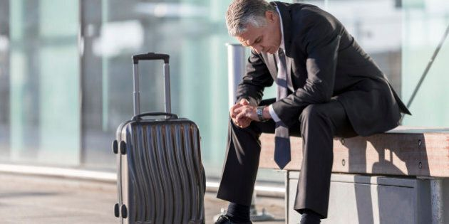 Exhausted businessman with baggage sitting outside airport