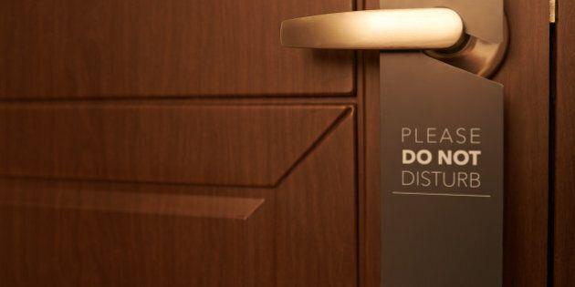 Closed door of hotel room with please do not disturb