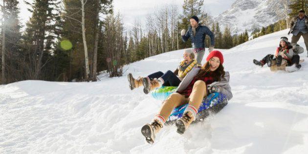Friends riding inner tubes in snowy field