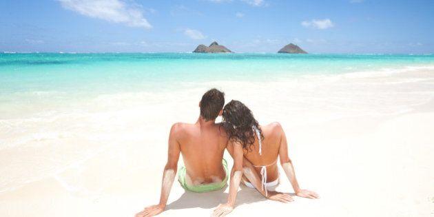 couple on beach vacation enjoying sun on honeymoon. Lanikai beach and the Mokulua islands in kailua,...