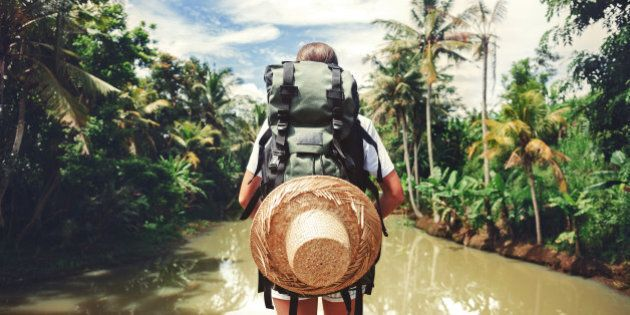 Traveler woman with backpack standing near big tropical river at sunny day