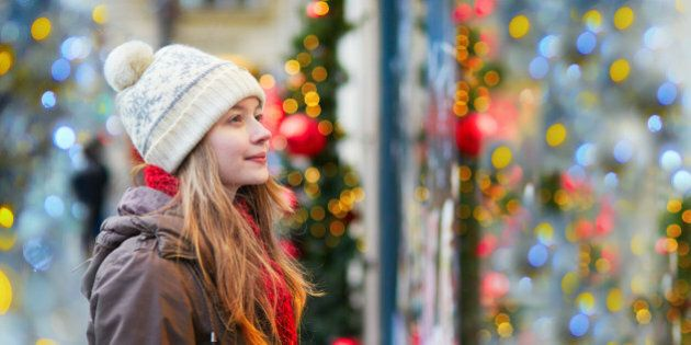 Girl on a Parisian street or at Christmas market looking at shop windows decorated for