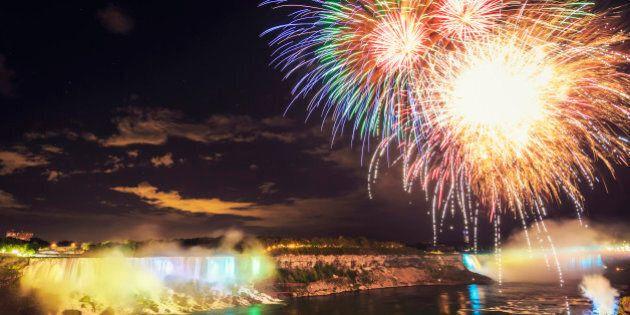 'Colorful Fireworks at illuminated Niagara Falls at Night. Niagara