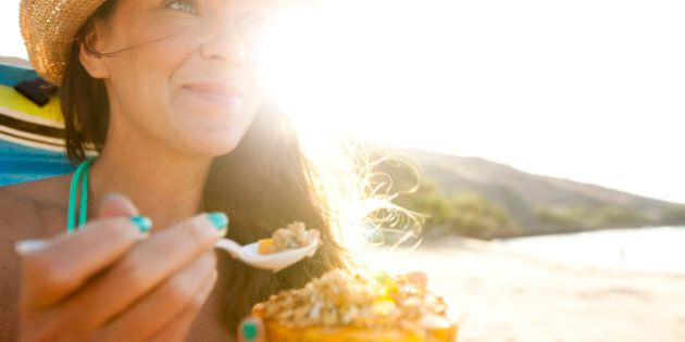 A beautiful woman with a straw hat eating a papaya with fresh granola and