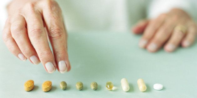 Mature woman arranging pills in
