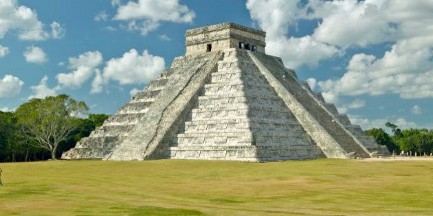White puffy clouds over the Mayan Pyramid of Kukulkan (also known as El Castillo) and ruins at Chichen...