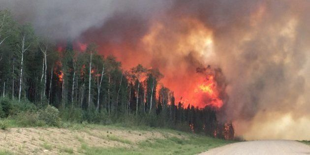 In this photo taken on Monday, June 29, 2015,  provided by the Saskatchewan Ministry of Highways and Infrastructure, forest fires throw flames above a tree-line along highway 969 in southern Saskatchewan, Canada.  Saskatchewan Premier Brad Wall says the province's firefighting budget has been depleted, but crews will keep working in the north, where flames and smoke have forced at least 3,000 people from their homes. (Saskatchewan Ministry of Highways and Infrastructure via The Canadian Press via AP) MANDATORY CREDIT