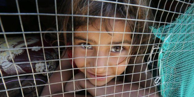 A young Syrian refugee girl looks out from her shelter at an informal refugee camp in the area of Zahrani,...