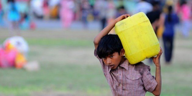 A Nepalese child carries a water can at a relief camp for survivors of the Nepal earthquake in Kathmandu...