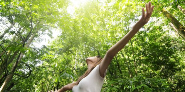 Enjoying the nature. Young woman arms raised enjoying the fresh air in green