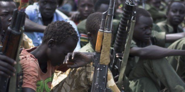 Young boys, children soldiers sit on February 10, 2015 with their rifles at a ceremony of the child soldiers disarmament, demobilisation and reintegration in Pibor oversawn by UNICEF and partners. UNICEF and its partners have overseen the release of another 300 children from the Cobra Faction armed group of former rebels of David Yau Yau. The children in Pibor, Jonglei State, surrendered their weapons and uniforms in a ceremony overseen by the South Sudan National Disarmament, Demobilization and Reintegration Commission, and the Cobra Faction and supported by UNICEF. They were to spend their first night in an interim care center where they will be provided with food, water and clothing. They will also have access to health and psychosocial services. AFP PHOTO/Charles LOMODONG (Photo credit should read CHARLES LOMODONG/AFP/Getty Images)