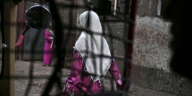In this Wednesday, Nov. 5, 2014 photo, an Egyptian woman seen from a motorized rickshaw walks on a street, near the home of 13-year-old Sohair el-Batea who died undergoing the procedure of female genital mutilation committed by Dr. Raslan Fadl, in Dierb Biqtaris village, on the outskirts of Aga town in Dakahliya,120 kilometers (75 miles) northeast of Cairo, Egypt. The latest survey on FGM rates, conducted in 2008, showed a prevalence rate of 91% for women aged 15-49. But that rate is lower for women aged 15-17, at 74%. (AP Photo/Nariman El-Mofty)