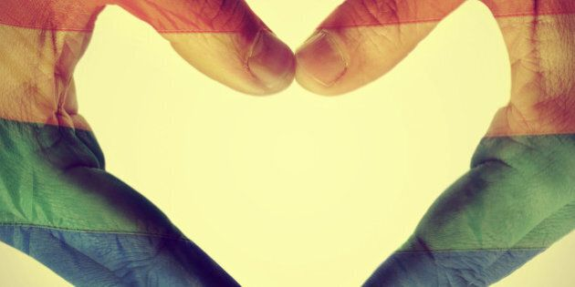 picture of man hands forming a hear patterned with the gay pride flag, with a retro