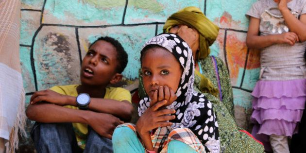 Displaced families who fled fighting in the southern city of Aden wait for relief supplies during a food...