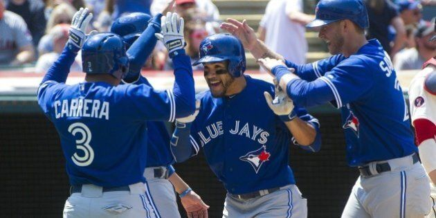 Toronto Blue Jays' Devon Travis, center, is greeted by teammates Ezequiel Carrera (3), Michael Saunders,...