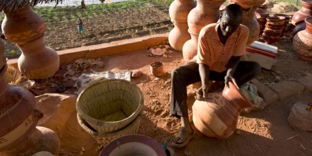 A craftsman paints water pots at his workshop on the banks of the river Bani, a branch of the river Niger,...