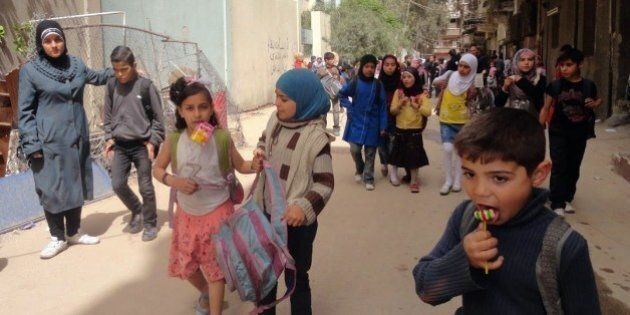 Palestinian children leave school after class on April 20, 2015 in the Yarmuk Palestinian refugee camp...