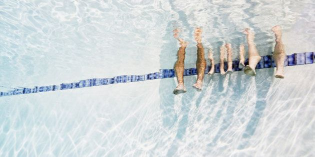 Family sitting on edge of pool resting feet in water underwater view