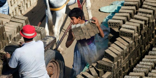 In this Oct. 17, 2012 photo, an Egyptian child loads a cart with cement bricks in a brick factory at...