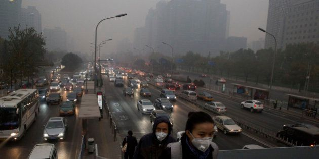 Pedestrians wear masks against the pollution as they cross an overhead bridge over a busy highway in...