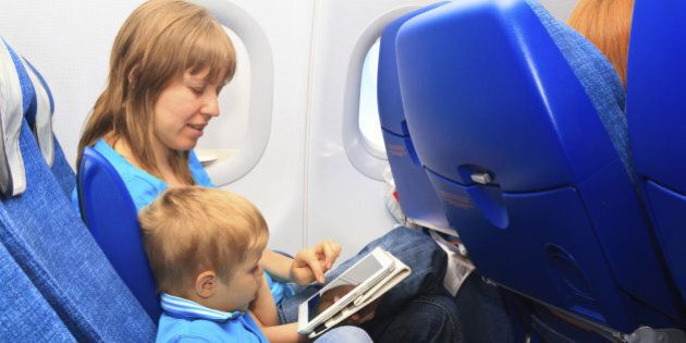 mother and son with touch pad in plane, family
