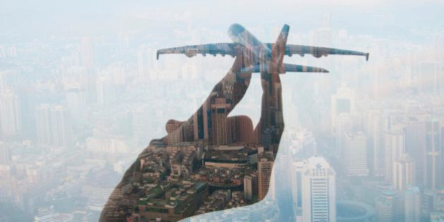 double exposure of mans hand holding a toy plane and cityscape in the