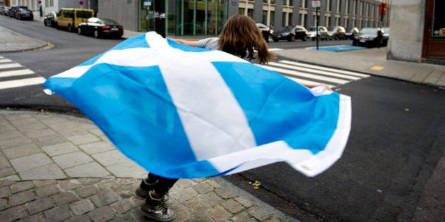 A young girl runs around a street pole with a Scottish national flag before taking part in a demonstration...