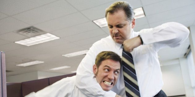 Two businessmen fighting in office, one in