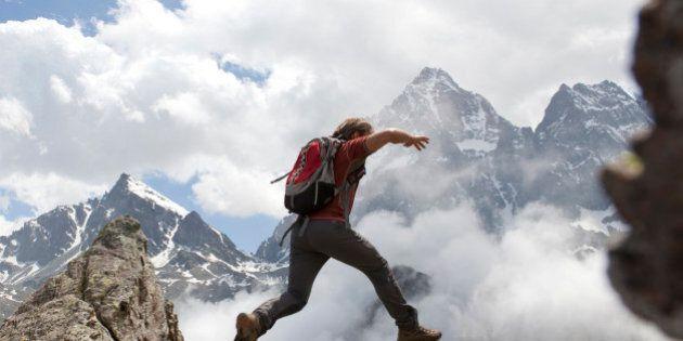 Hiker jumps across rock gap, mountains