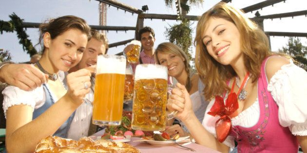 young people in traditional costumes drinking beer on the Octoberfest