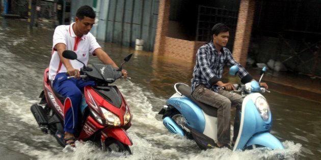 Thai men ride their motorbikes through flood waters following heavy rains in Thailand's southern city...