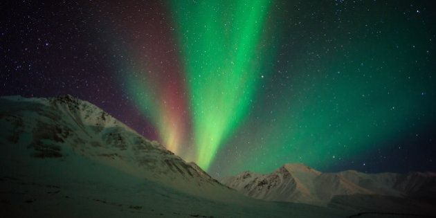 Aurora borealis ( northern lights ) above Alaskan Mountain. This shot was taken at Atigun Pass, Dalton...