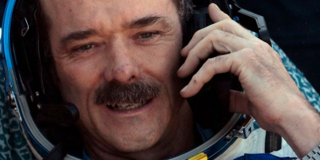 Canadian astronaut Chris Hadfield, speaks on cell phone shortly after the landing of the Russian Soyuz...