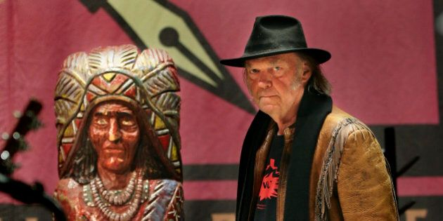TORONTO, ON - JANUARY 12:  Neil Young walks into the news conference past a cigar store Indian. Famed singer, Neil Young held a news conference on Jan. 12 to tout his benefit concert that same day raising money and awareness for the Athabasca Chipewyan First Nation Legal Defense Fund.  The event was held at Massey Hall.January 12, 2014.        (Richard Lautens/Toronto Star via Getty Images)
