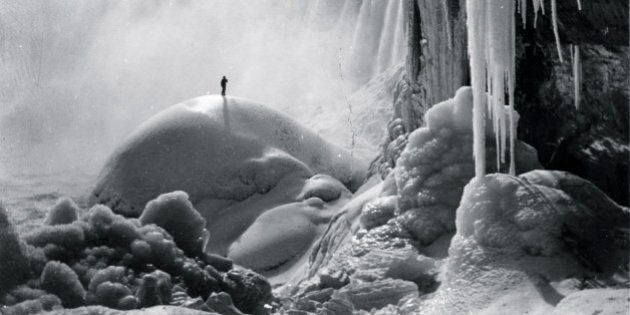 UNSPECIFIED - CIRCA 1903: Sole Adventurer stand on an ice dome beneath the icicled Niagara Falls in a...
