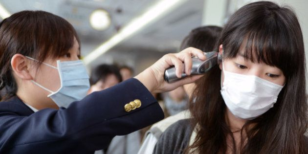 A passenger (R) has her temperature checked by a Centers for Disease Control (CDC) staff member at the...