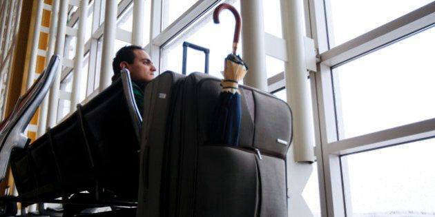 Traveler Younsi Yassine waits for another flight to New York after a cancellation at Reagan National...