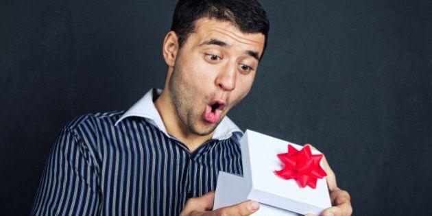 Surprised man opening big gift box