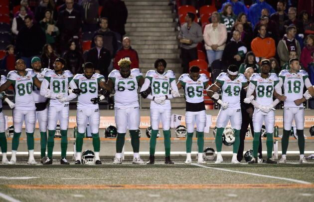 Saskatchewan Roughriders players link arms during the singing of