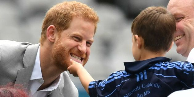 The Duke of Sussex has his beard stroked by a small child in Croke Park on the second day of his visit...