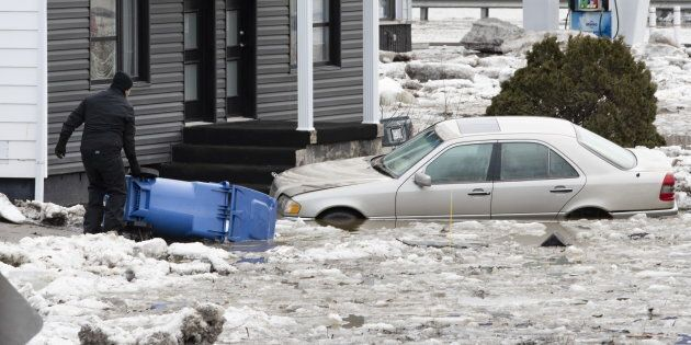A man picks a recycling bin from the parking lot by a flooded car on April 16, 2019 in Beauceville