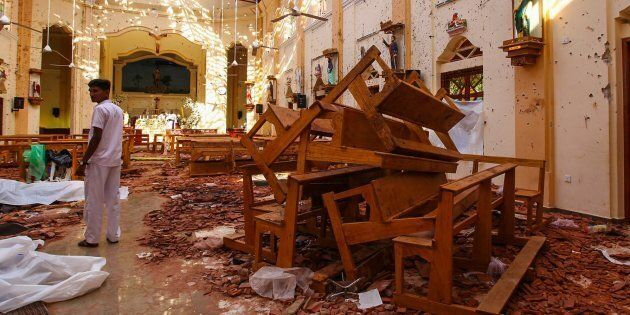 Officials inspect the damaged St. Sebastian's Church after multiple explosions targeting churches and...