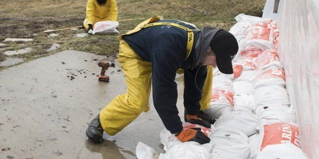 Workers lay down sandbags as flood waters rise in