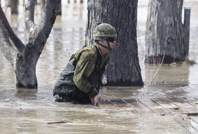 A member of the Canadian armed forces removes a wooden platform from a street surrounded by floodwaters...