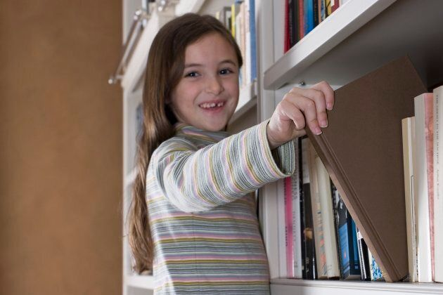 A girl pulls out a book at a Toronto library.