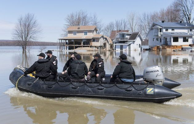 Members of the Naval Reserve patrol the Ottawa river next to homes surrounded by floodwaters in the town...