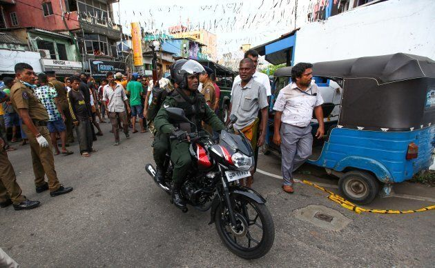 Sri Lankans security forces are seen at the site following an explosion in a vehicle parked near St....