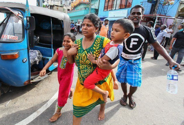 Sri Lankans living near St. Anthony's shrine run for safety after police found explosive devices in a...