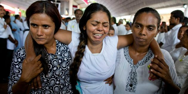 A grieving woman is supported during a funeral service at St. Sebastian Church in Negombo, Sri Lanka,...