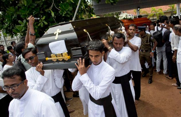 Clergymen carry coffins for burial during a funeral service for Easter Sunday bomb blast victims at St. Sebastian Church in Negombo, Sri Lanka, on April 23, 2019.